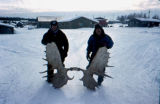 Joe Redington Sr. and man in Kaltag holding moose rack during Joe Redington Sr.'s Iditarod...