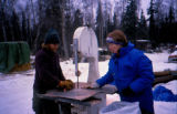 Two people cutting meat for Joe Redington Sr.'s Iditarod Challenge.