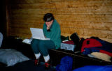 Jeanne Ashcraft using a laptop in cabin during Joe Redington Sr.'s 1995 Iditarod Challenge.