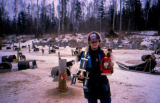 Junior musher Melissa Garrison with race trophies, standing in dog yard.