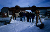 Joe Redington Sr. and other Iditarod Challenge participants under the burled arch in Nome.