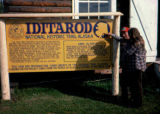 Joe Redington Sr. and woman in front of the Iditarod National Historic Trail Sign.