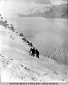 Two men ascending by side of Valdez Glacier with aid of a rope.