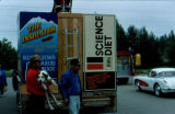 Duane Lambert, sled dog named Luna, and Joe Redington Sr. behind a dog truck at the Colony Days...