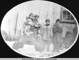 Eskimo children with wooden tricycle.