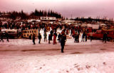 Dog trucks, mushers, dogs, and spectators gather at Tudor Track for the start of the 1973 Iditarod...