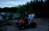 Garrisons riding on a four-wheeler ATV down dirt road in Knik.
