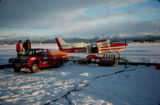 Small red pickup truck parked next to an airplane on frozen lake ice.