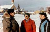 Three men stand outdoors in village.