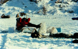 Musher lying inside dog sled, taking a break on the Iditarod Trail.