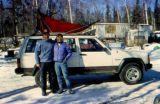 Dale Meyers and Rebecca Meyers pose in front of car with a dog sled on top.