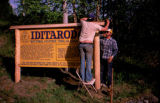 Two men working on Iditarod National Historic Trail marker.
