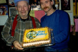 Joe Redington Sr. standing with Jerry Aarnodt, holding cake for Joe Redington Sr.'s birthday.
