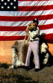 Joe Redington Sr. posing with sled dog Tang in front of an American flag.