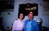 Joe Redington Sr. poses next to a woman in a room with Iditarod memorabilia on the wall.