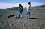 Two women standing with sled dog puppies on gravel.