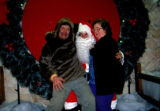 Vi and Joe Redington Sr. pose while sitting on Santa's lap.