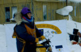 Female musher stands on runners of dog sled during Serum Relay Race.