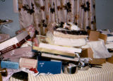 Stack of wedding gifts for Joe Redington Jr. and Thela on a bed.