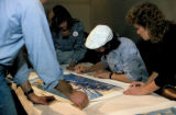 1984 Iditarod champion Dean Osmar signs a print of Machetanz's 'Reaching the Pass.'
