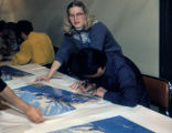 Iditarod champion Emmitt Peters signs a print of Machetanz's 'Reaching the Pass.'