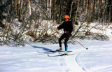 Man skis on a flat snowy surface.