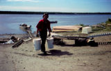 Bill Cotter holding buckets of fish on a river bank.