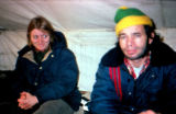 Woman and man sit inside of a tent.