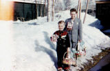 Tim Redington and Joe Redington Jr. stand outside in snow with Easter baskets and chocolate eggs.