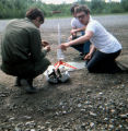 Three people crouch on gravel area, working on what looks like a model rocket.