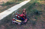 Young girl sits on grass next to her red tricycle.