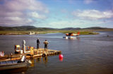 Two people stand on dock in Unalakleet and watch float plane.