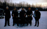 Five men pose with trophies standing next to car outside in winter.