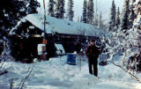 Dick Mackey poses in front of log cabin in Rohn Checkpoint on the Iditarod Trail Sled Dog Race.