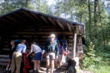 Hikers outside of log cabin along Chilkoot Trail.