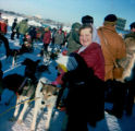 Vi Redington poses next to sled dog team at the start of Iditarod Trail Sled Dog Race.