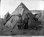 Eskimos and their igloo on sandspit, Nome, Alaska.