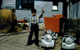 Boy stands next to what may be two small engines or outboard motors.