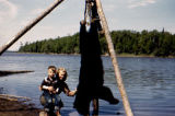 Vi and Tim Redington pose next to a dead black bear, hanging from wooden tripod.