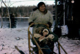 Margaret Saccheus poses on back of dog sled with Joe Redington Jr. and baby Keith Redington seated...