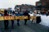 School children carry 'Everyone Loves a Musher' banner past the burled arch in Nome at the end of...