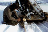 Joe Redington Sr. rough-locking the runners of his dog sled before hauling wings of Cessna 180 by...