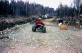 Man on three-wheeler ATV on gravel by Joe Redington Sr.'s dog lot in Knik.