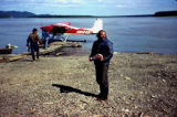 People on shore and walking on dock toward Cessna 180H airplane.