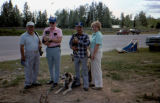 Joe Redington Sr. poses with tourists, along with sled dog and sled dog puppies.