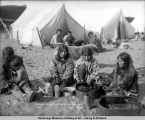Eskimos eating breakfast on the sandspit, Nome, Alaska.