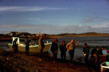 People stand on shoreline in Unalakleet, to receive boat load of herring.