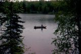 Two people fishing in wooden boat on Flathorn Lake.