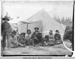 Native family in front of canvas tent.