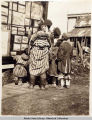 [Eskimo family looking at display of photographs] ca. 1903